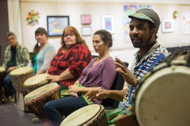Mitch Endioc (left), Susan Freeman, Beth Maccombs and Kathryn Cooper listen to Lawrence R Greene (right) as he instructs them on technique and style during their Ugata drum class in Arts West in Athens, Ohio. Greene has practiced and played the drums for seven years and began teaching this class two years ago. (HANNAH SCHROEDER   FOR THE POST)