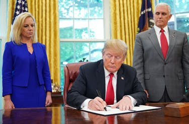"Watched by Homeland Security Secretary Kirstjen Nielsen (L) and Vice President Mike Pence, US President Donald Trump signs an executive order on immigration in the Oval Office of the White House on June 20, 2018 in Washington, DC. - US President Donald Trump on Wednesday signed an executive order aimed at putting an end to the controversial separation of migrant families at the border, reversing a harsh practice that had earned international scorn.""It's about keeping families together,"" Trump said at the signing ceremony. ""I did not like the sight of families being separated,"" he added. (Provided via MANDEL NGAN/AFP/Getty Images)"