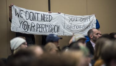 Protesters hold banners during the open forum on the interim 'Freedom of Expression' policy in Baker Ballroom on March 21. (FILE)