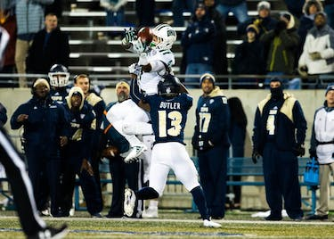Ohio's Papi White (4) misses the ball while being taken down by Akron's Denzel Butler (13) during the last quarter of the Ohio-Akron football game. The Bobcats lost the game 37-34 (MIJANA MAZUR | FOR THE POST)
