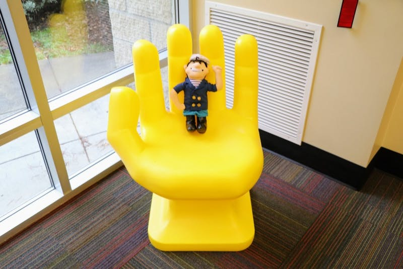 The Handshake yellow hand chair holds a Wally the Pilot.