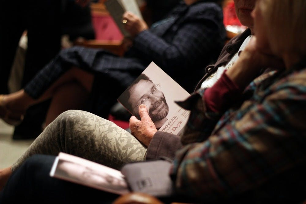 Audience members glanced at a booklet while waiting for the speakers to begin at Thursday's Celebration of the Life and Work of Brian Doyle.