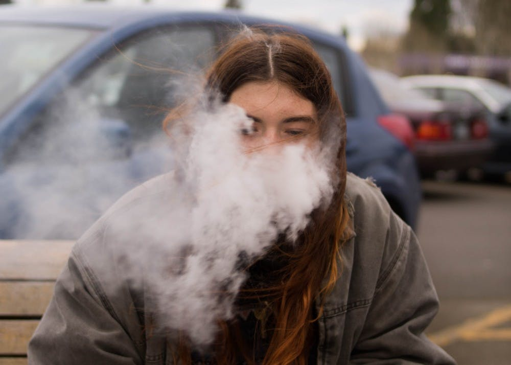 A University of Portland student uses a tobacco vaporizer between classes. Under a new Oregon law, it is illegal for people under 21 years old to use, possess or purchase tobacco products.