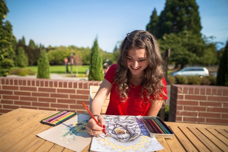 Alina Bogachuk smiles as she draws for the Beacon. Bogachuk has 188,000 followers on Instagram and mostly draws landscapes and people.