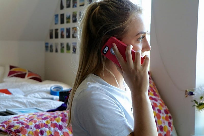Junior Kiley Gersch attempts to make a phone call in Lund Family Hall.