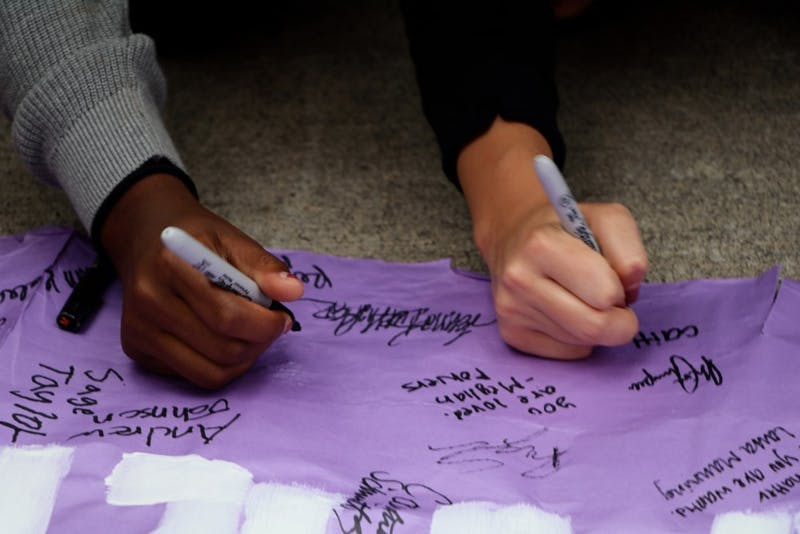"Students sign a purple ""#IStandWithDreamers"" banner to show their support for those affected by the rescindment of DACA."