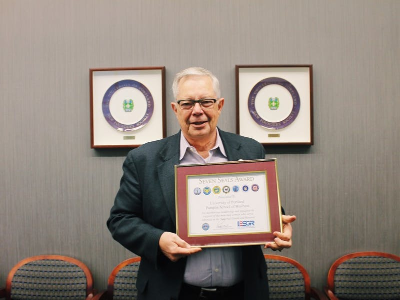 Dr. Robin Anderson, Dean of the Pamplin School of Business Administration, holds the Seven Seals Award that the business school was recently awarded.