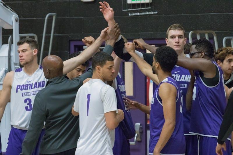 The men's basketball team breaks before starting their morning practice.