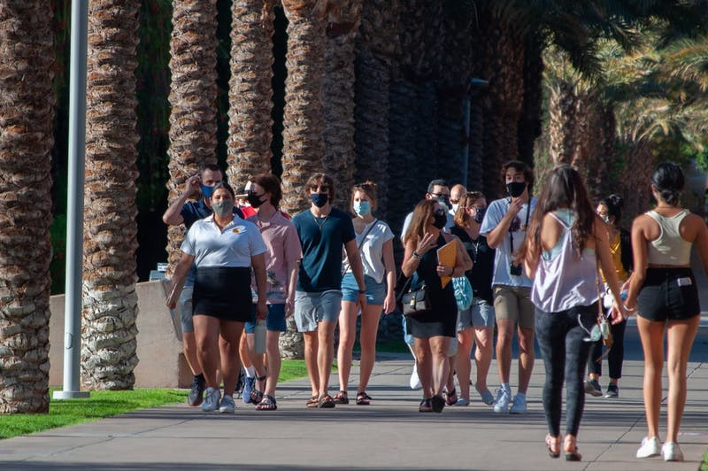 Masked students walk down Palm Walkin Tempe, Arizona.