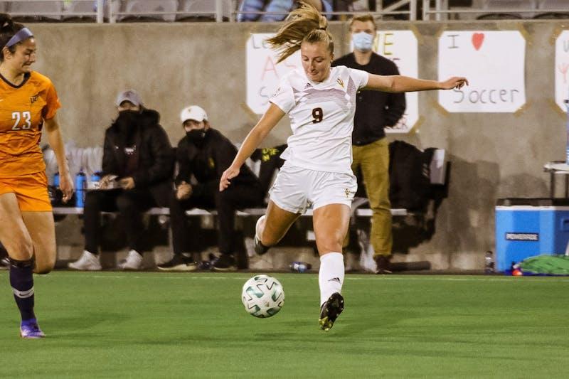Nicole Douglas kicks a soccer ball down the field.