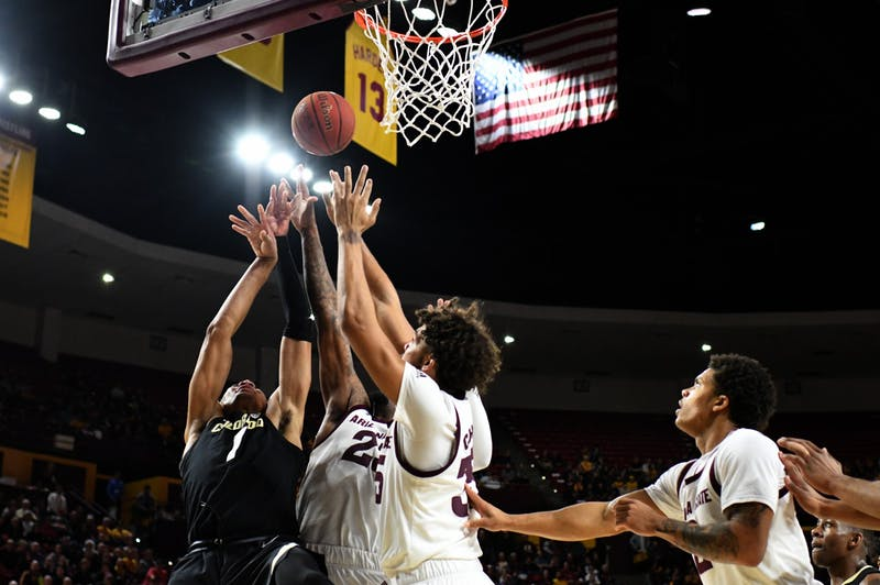 Basketball players jump for the ball under the hoop.