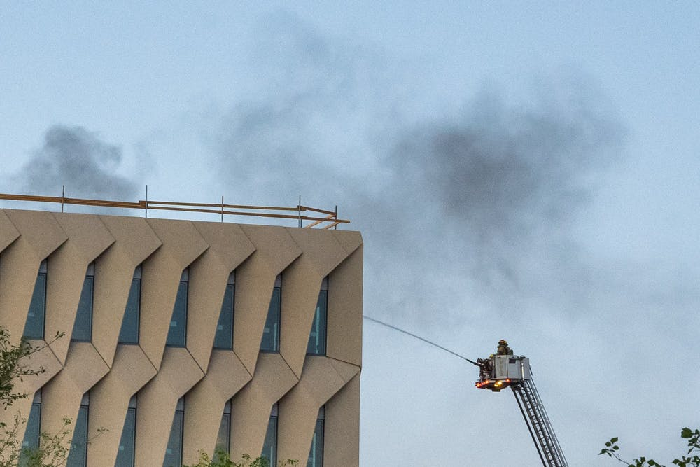 Firefighters battle a fire on the roof of Interdisciplinary Science and Technology Building 7