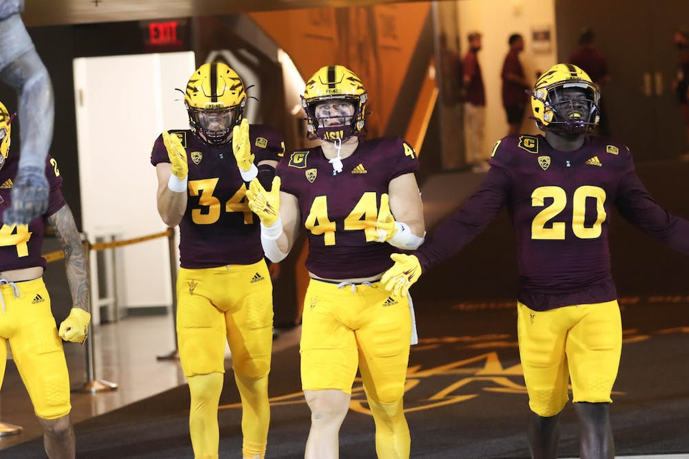 Three ASU football players walking onto the field clapping and pumping up the crowd.