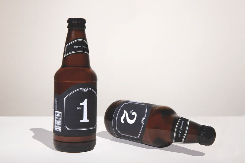 A photo illustration depicting two bottles of beer labeled, first dose and second dose.