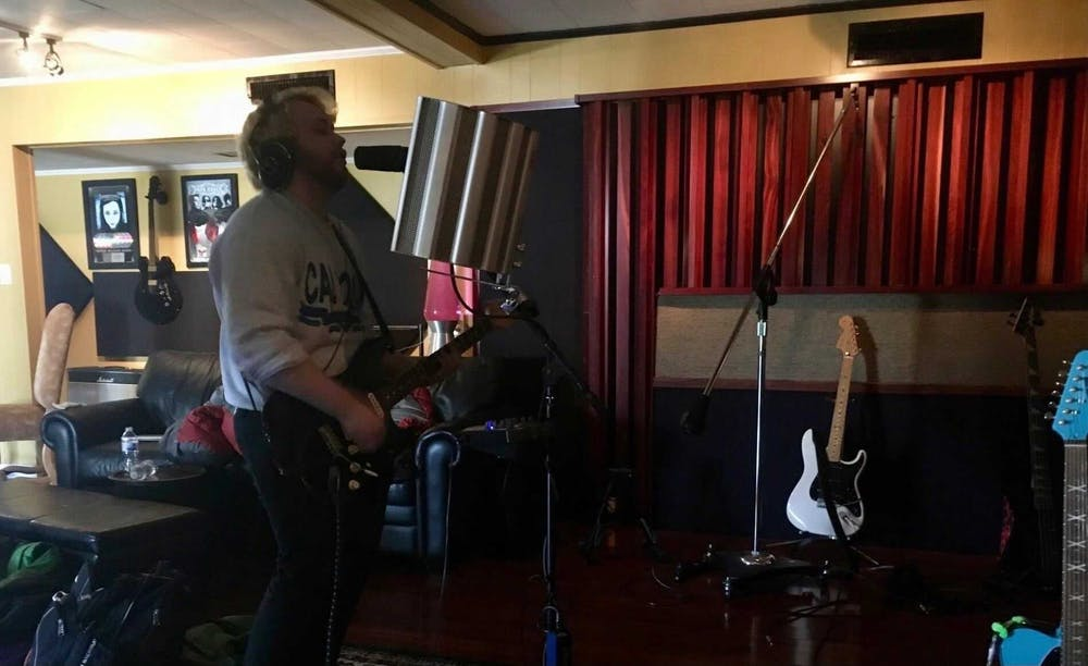 Vaughan Jones practices playing guitar in a recording studio.