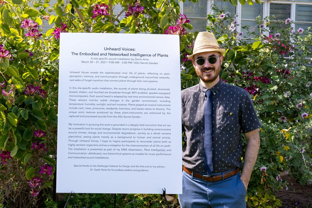 """Devin Arne poses for a portrait in front of a sign detailing his exhibit: 'Unheard Voices: The Embodied and Networked Intelligence of Plants"""""""