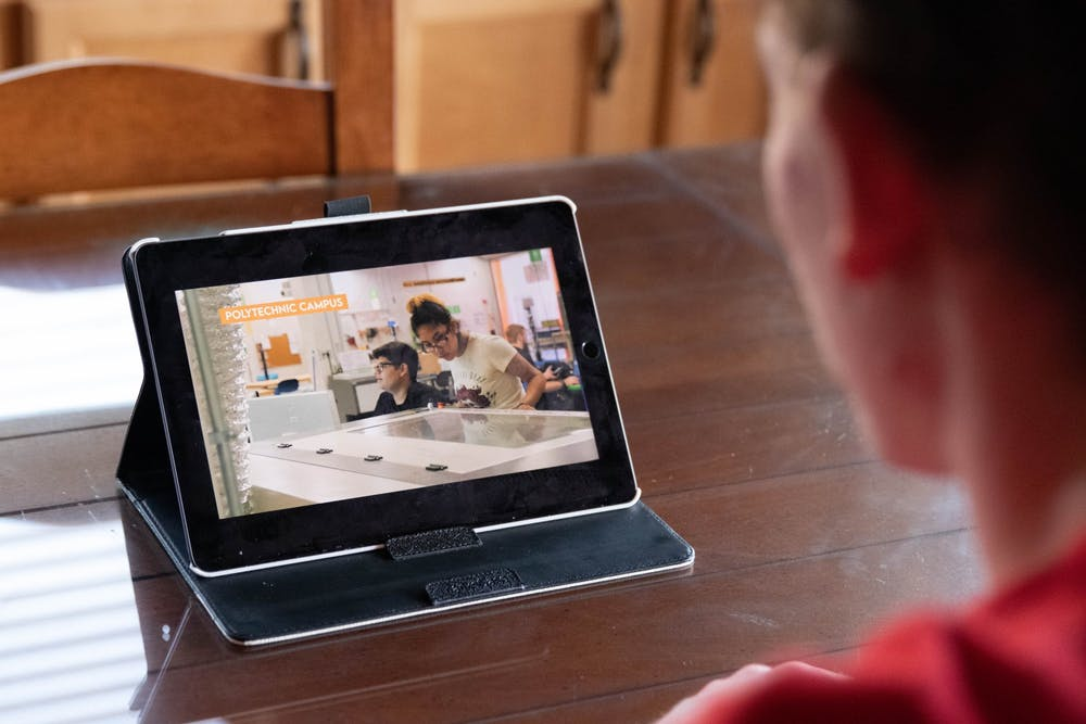 """Owen Dow watches the ASU episode of """"The College Tour"""" on his tablet."""