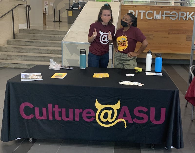 Brielle Ruscitti and Jasmine Smalls pose for a photo in front of a Culture @ ASU table