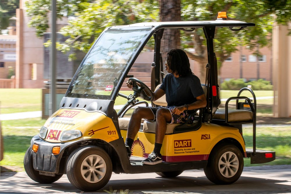 ASU DART cart driver drives a gold and red cart.