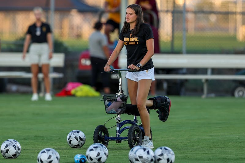 Keri Matthews, who wears a brace due to an ankle injury, walks amongst a field of soccer balls prior to a soccer game.