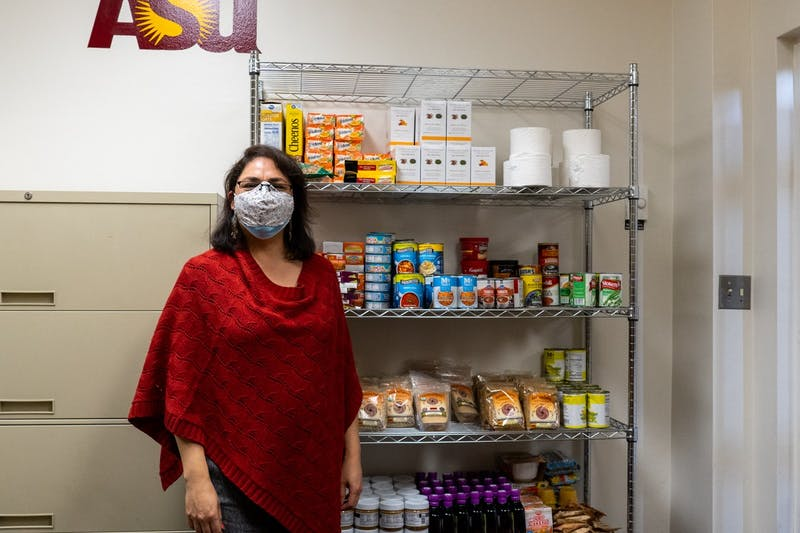 Laura Gonzales-Macias poses for a photo in front of shelves filled with food.