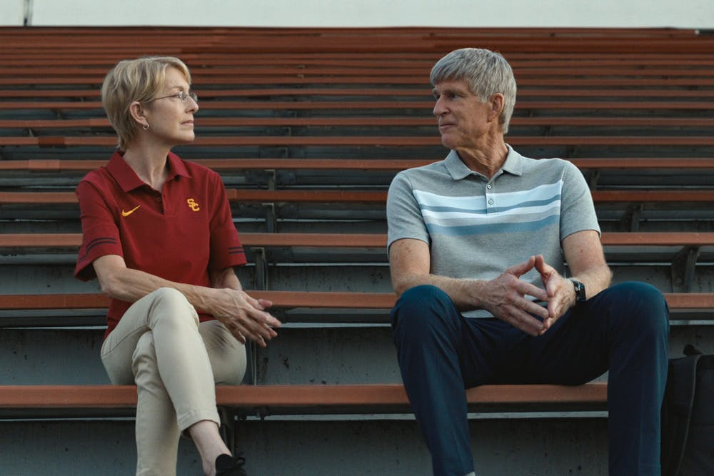 A scene of two people on a bleacher from Operation Varsity Blues The College Admissions Scandal is shown.