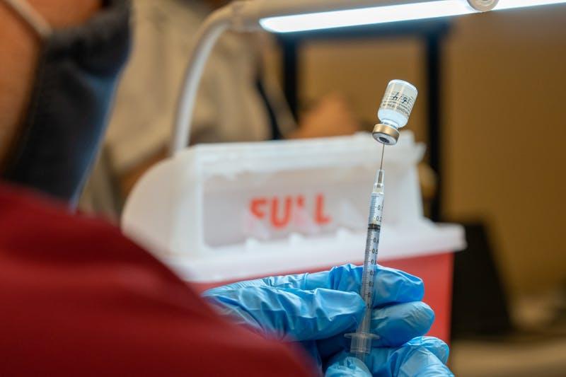 El farmacéutico Trevor Lawrence llena una jeringa con una dosis de la vacuna Pfizer COVID-19