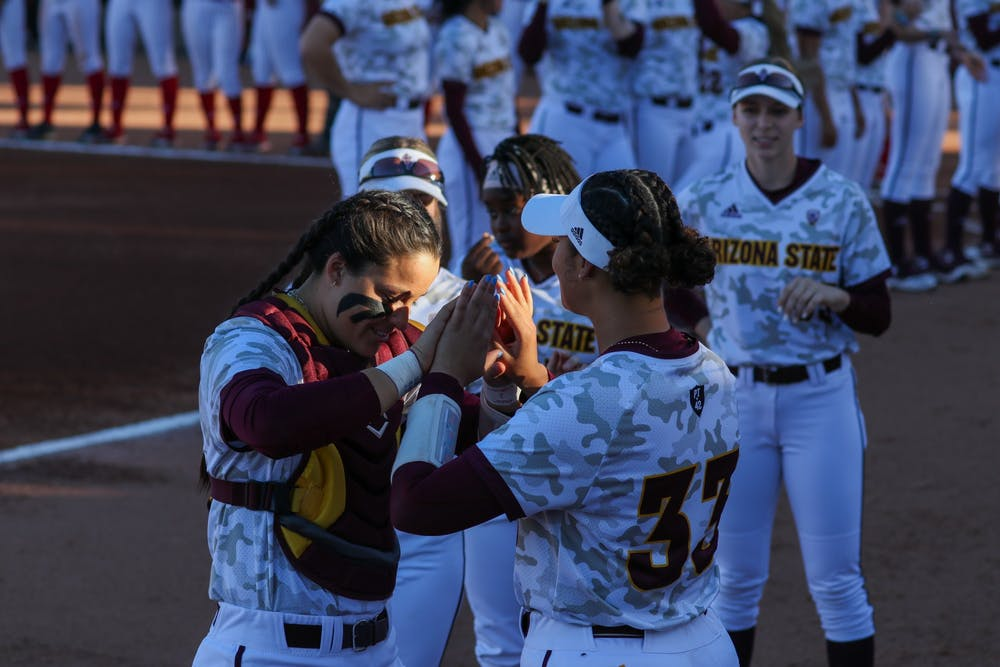 Maddi Hackbarth (23) Denae Chatman (33) high-five before the game against Nebraska State