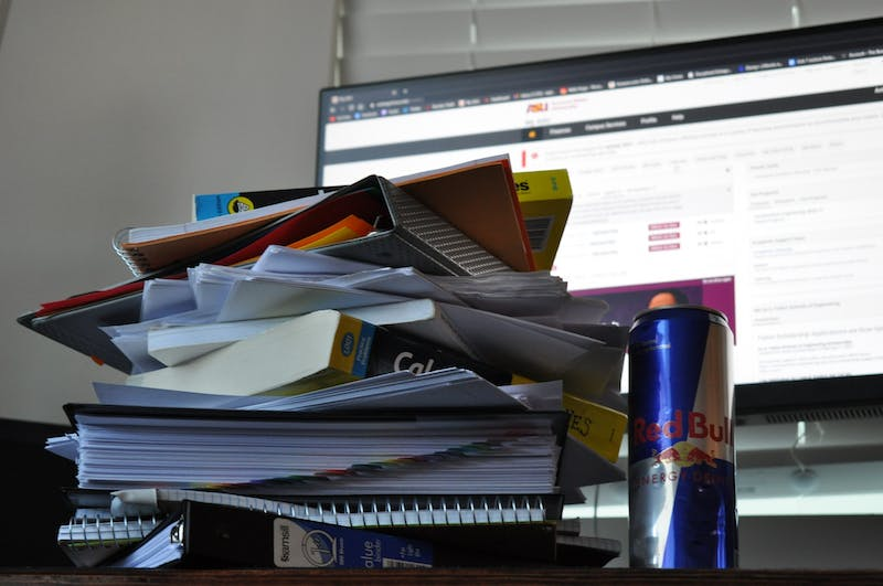 A stack of papers, textbooks and a RedBull sat atop a desk.