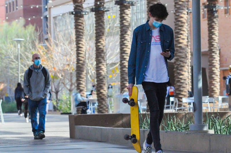 An Arizona State University student walking with a skateboard and a mask on campus.