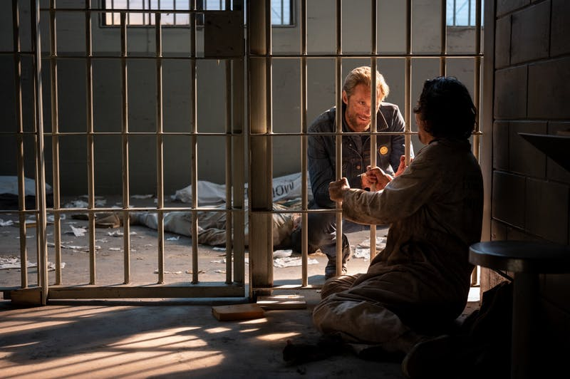 Alexander Skarsgård crouches in front of a jail cell for a scene of The Stand.