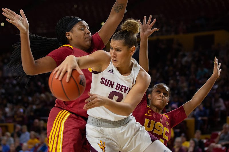 ASU now-senior guard Taya Hanson (0) looks to pass the ball while being blocked by players from USC