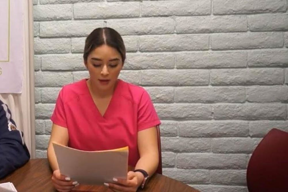 Marilyn Baez reads off papers while sitting at a table