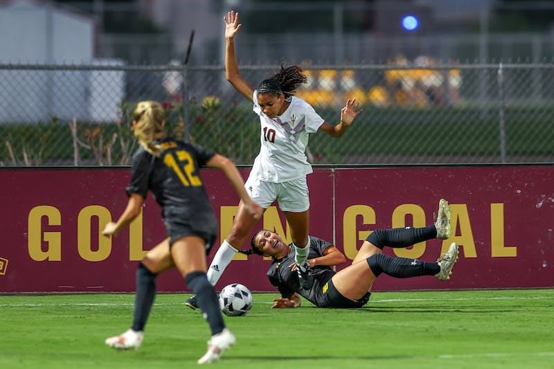 A Southeastern Louisiana player falls to the ground as ASU graduate student defender Jayda Hylton-Pelaia fights for the ball.