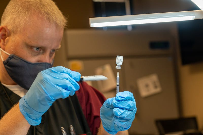 Pharmacist Trevor Lawrence fills a syringe with a dose of the Pfizer COVID-19 vaccine