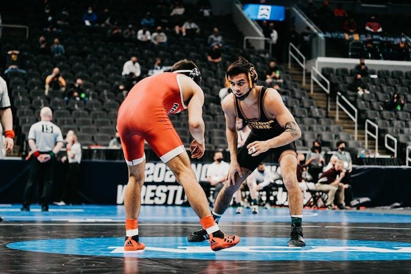 ASU wrestler Brandon Courtney looks down North Carolina State wrestler Jakob Camacho