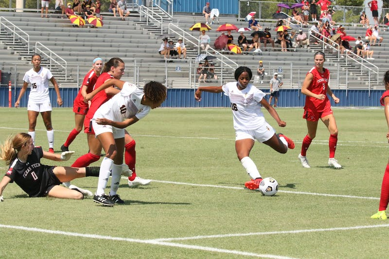 ASU player in a white uniform kicks the ball. She is surrounded by Texas Tech players in red.