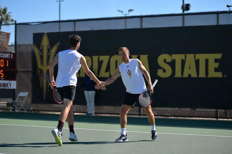 Nathan Ponwith congratulates freshman Max McKennon during a doubles match