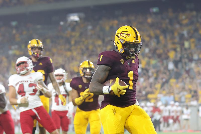 ASU football player, number one, runs ball into the end zone. There are players behind him trying to defend him, and chasing him.