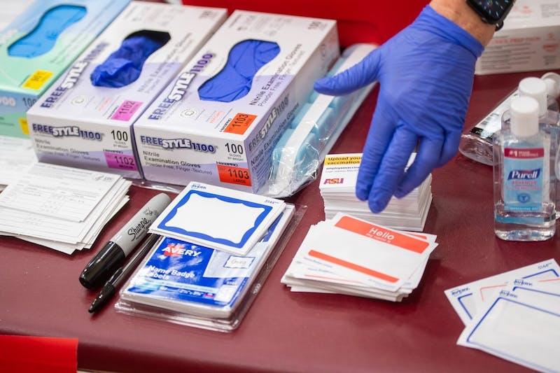 Una mano enguantada señala objetos sobre una mesa donde las personas pueden recibir la vacuna COVID-19.