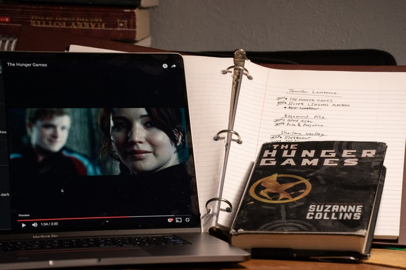 A scene of the hunger games book, Jennifer Lawrence in the Hunger Games movie, and a notepad.