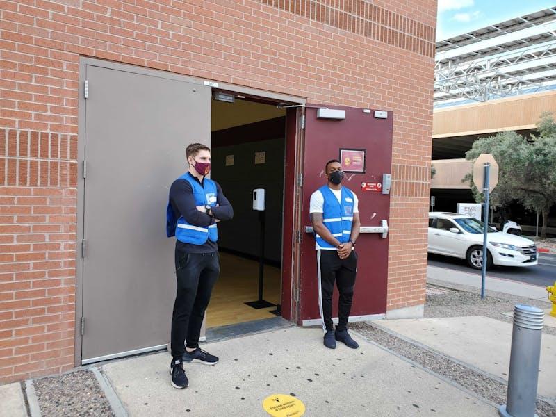 Anthony Rivera, estudiante universitario de tercer año, que está estudiando ejercicio y bienestar, y Jack Frus, que está estudiando salud y las ciencias políticas, son voluntarios en el sitio de vacunas de COVID-19.