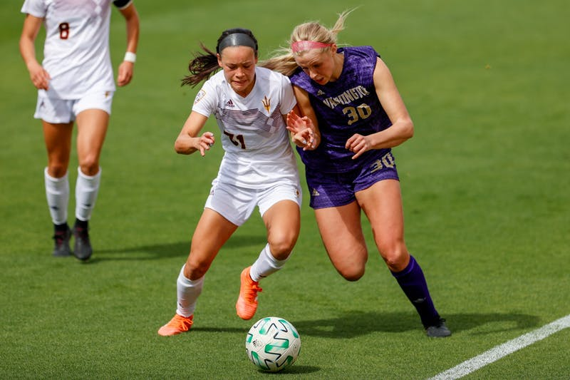 Players from ASU and Washington fight the the ball on soccer field.