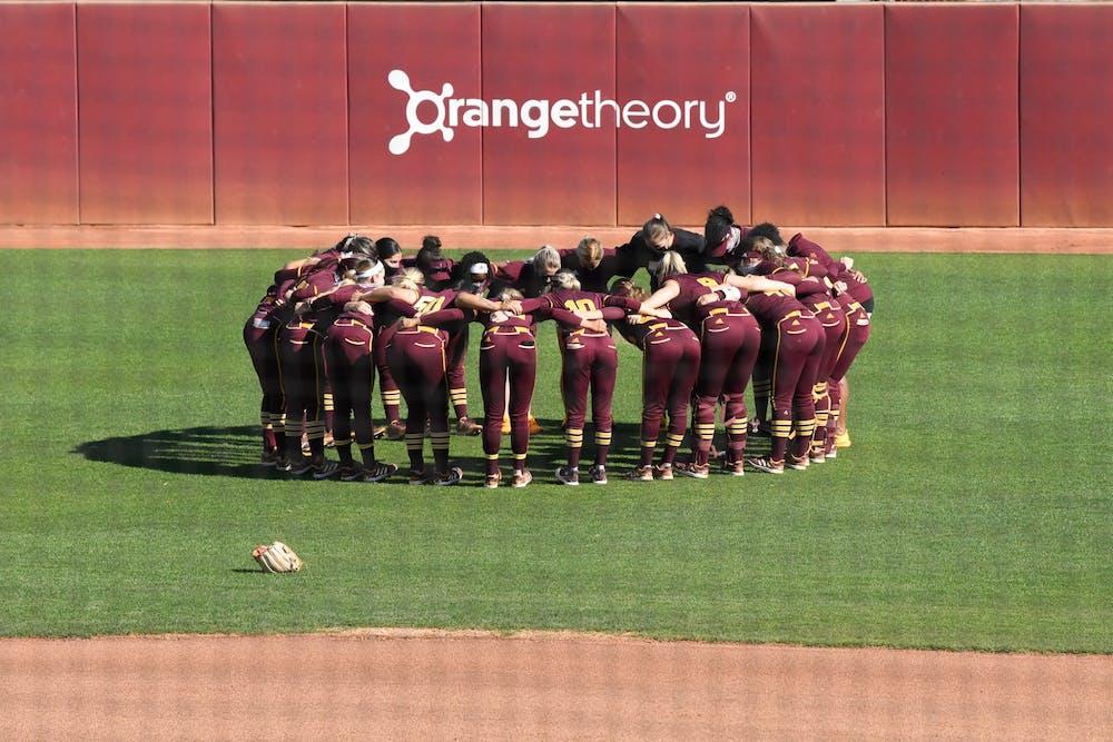 The ASU softball team huddles on the field