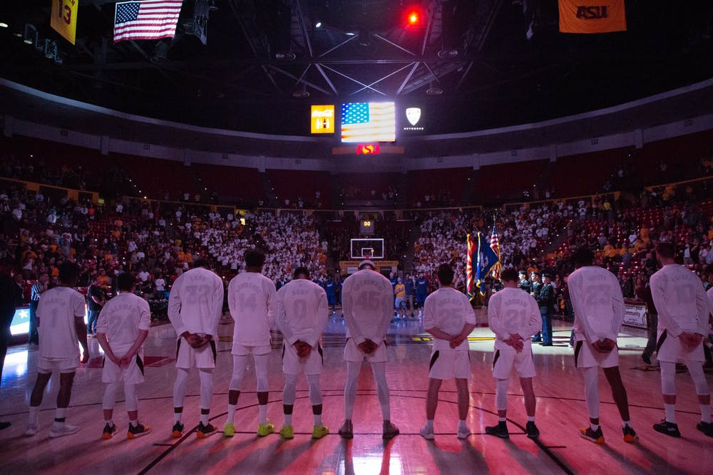 Basketball players lined up in purple lighting for the national anthem.
