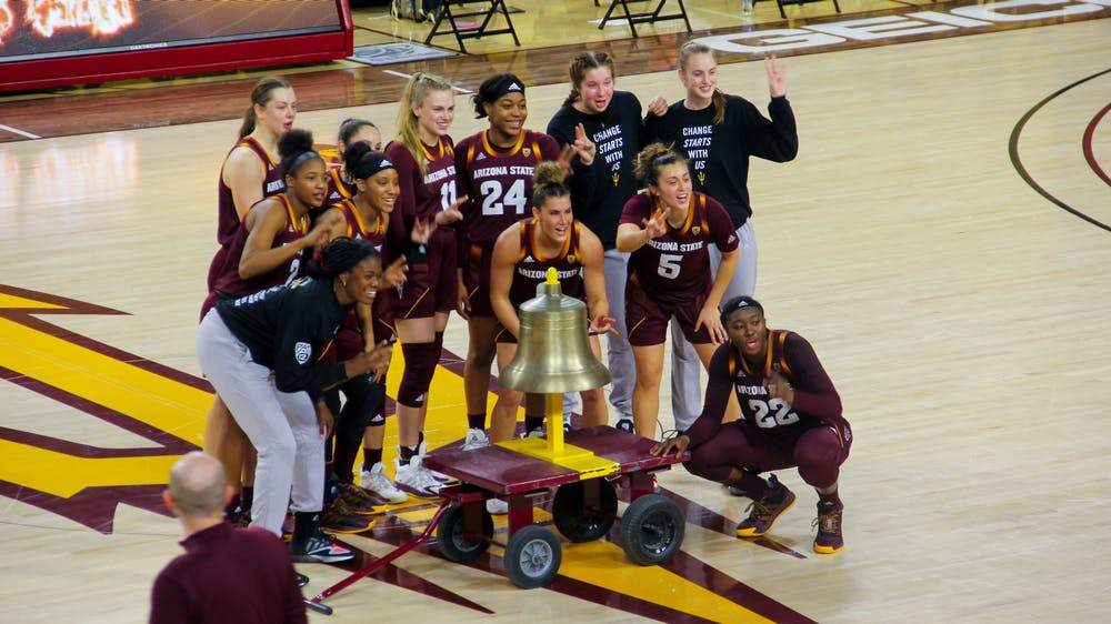 The ASU Women's Basketball team rings a bell following a victory over Colorado