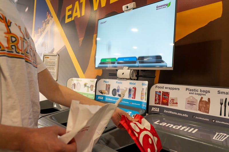 A student throws their trash away in the new OSCAR Sort machine