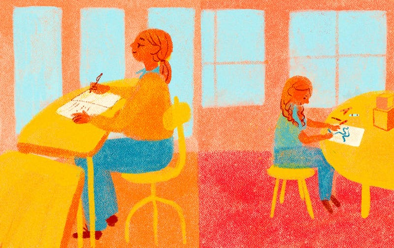 A parent and a child both sit at desks working back-to-back.