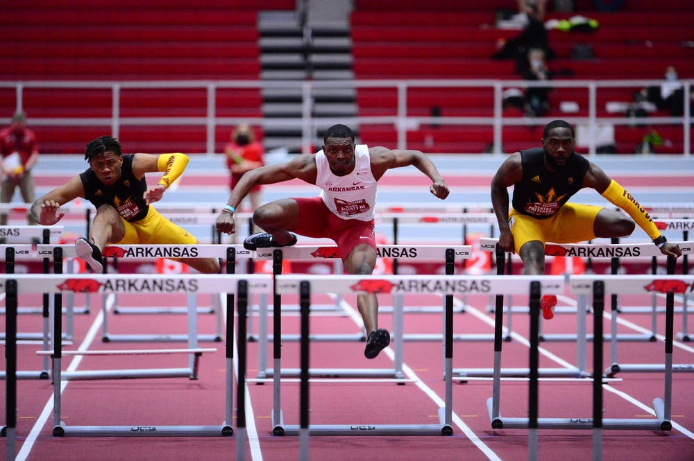 Jamar Marshall Jr. (left) and senior Kentre Patterson (right) jump over hurdles during a track meet.