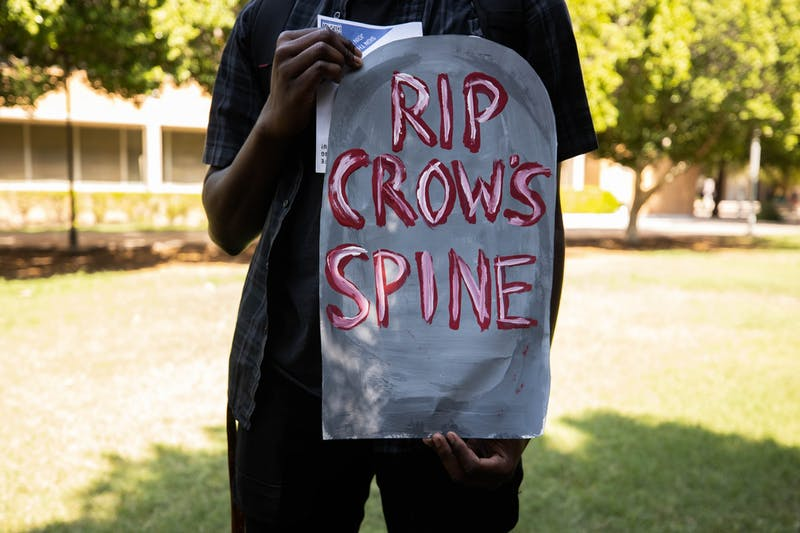 """Demonstrator holds a tombstone with the statement """"RIP Crows Spine,"""" written in red."""